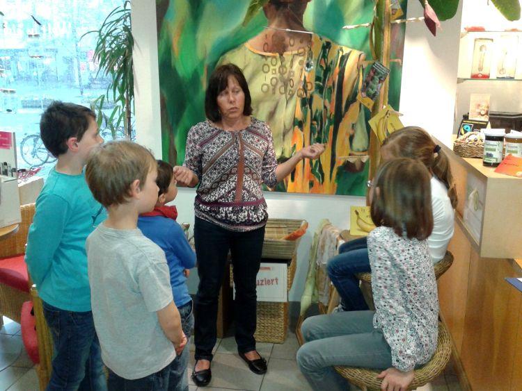 Die Kinder bestaunen zusammen mit Birgitt Rupp vom Eine-Welt-Laden den Bananenbaum.