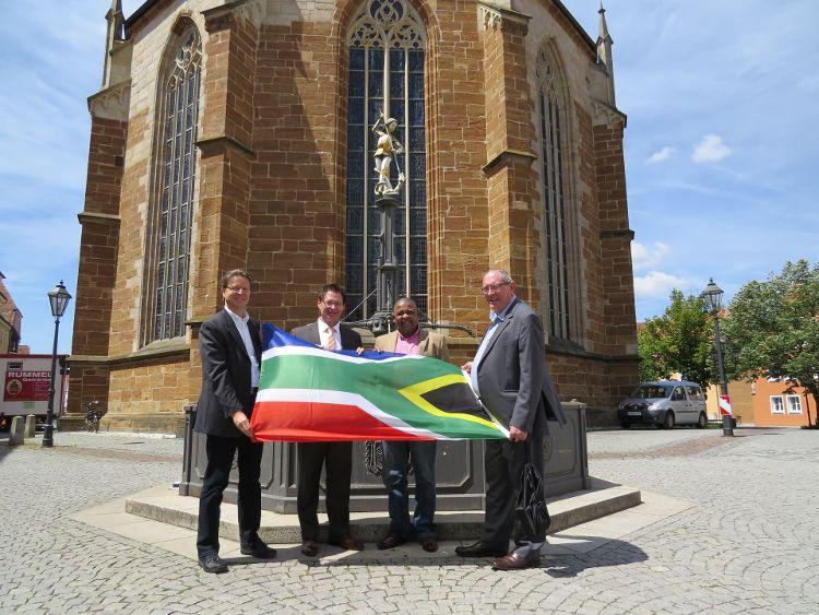 Ralf Mützel, Leiter des Amtes für Nachhaltigkeitsförderung, Oberbürgermeister Thomas Thumann, Bürgermeister Conrad Poole und Stadtrat Dr. Lourens Du Toit mit der südafrikanischen Flagge vor dem Münster St. Johannes.