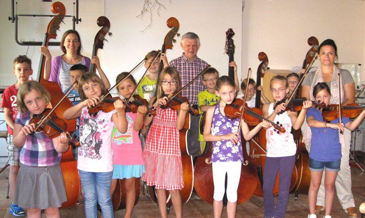 Eva Diepenseifen (Bürgerstiftung), Werner Brunner (Rektor), Sonja Bergold (Bürgerstiftung) zusammen mit Kindern der musikalischen Grundschule Pölling