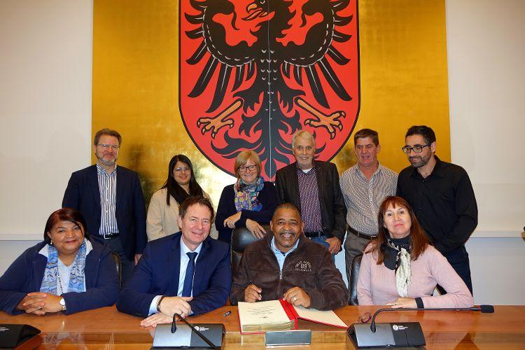Eintrag ins Goldene Buch durch Bürgermeister Conrad Poole, auf dem Foto links daneben Oberbürgermeister Thomas Thumann. Daneben und dahinter die Vertreterinnen und Vertreter der beiden Städte Neumarkt und Drakenstein.